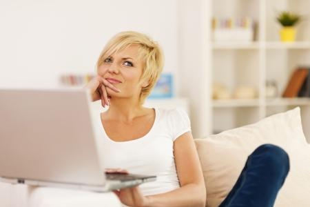mujer pensativa: Retrato de la mujer pensativa con el ordenador port�til