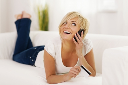 Young woman talking on mobile phone and holding credit card  photo