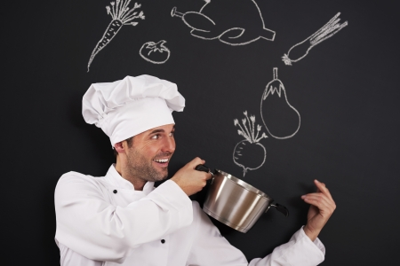 chef cooking: Handsome chef catching ingredients for soup