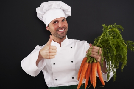 Chef with bunch of carrots showing thumbs up photo