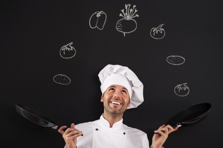 chefs whites: Handsome chef jugglery with vegetable Stock Photo