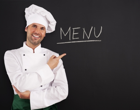 chefs whites: Handsome chef showing menu Stock Photo