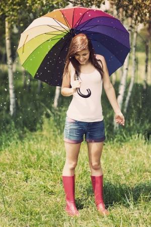 botas de lluvia: Mujer sonriente en día de lluvias de verano