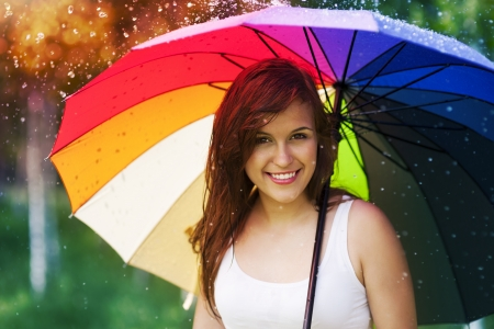 Portrait of beautiful and smiling woman with umbrella photo