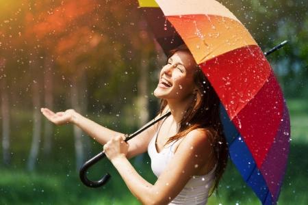 Lachende vrouw met paraplu controleren op regen Stockfoto