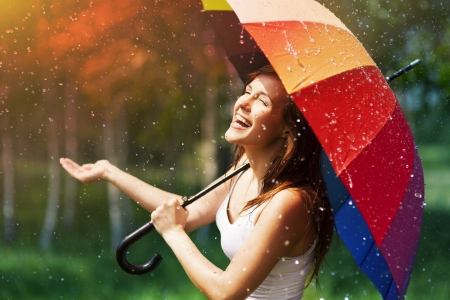 sonrisa: Riendo mujer con paraguas comprobaci�n de la lluvia Foto de archivo