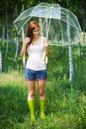 Smiling woman in rainy summer day in forest