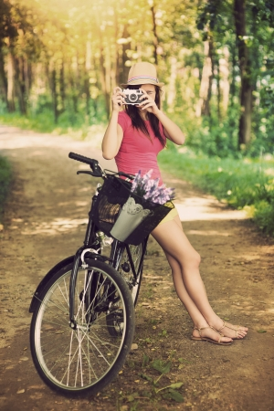 nature photography: Young woman on bike photographing nature Stock Photo