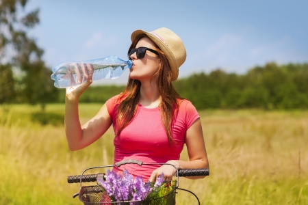 Active woman with bike drinking cold water photo