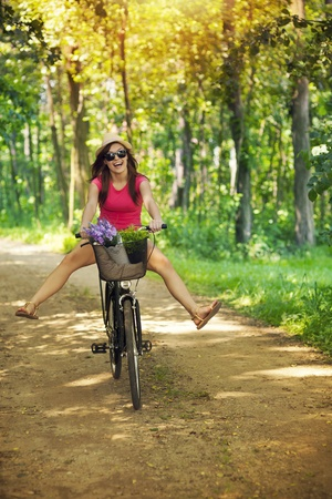 Happy woman enjoying a cycle ride in forest photo