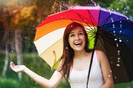 lluvia paraguas: Mujer sorprendida con el paraguas en la lluvia de verano Foto de archivo
