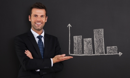 Smiling businessman presenting graph on blackboard  Stock Photo - 20614205