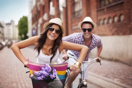 jovenes enamorados: Feliz pareja en bicicleta en la ciudad Foto de archivo