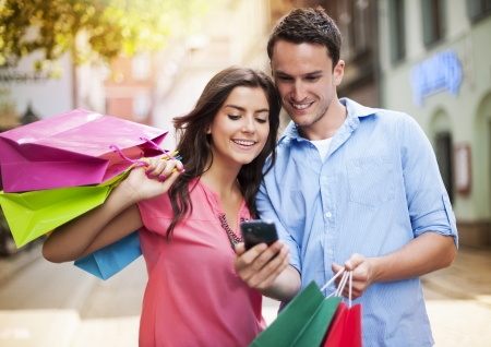 retail scenes: Young couple with shopping bag using mobile phone  Stock Photo