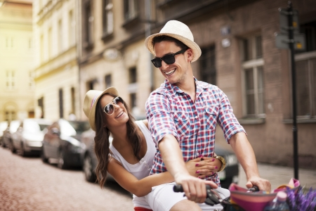 recreational pursuit: Handsome man taking his girlfriend on bicycle rack