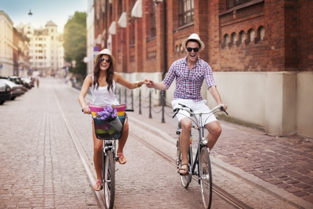 city alley: Happy young couple holding hands and riding on bike