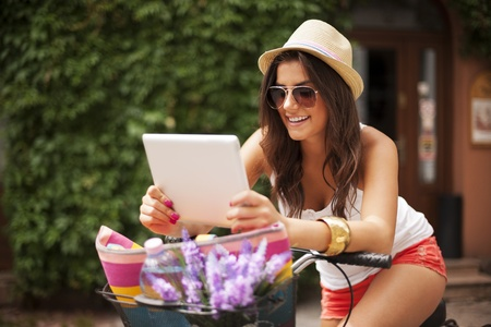 hapiness: Woman leaning on bike and checking something on tablet