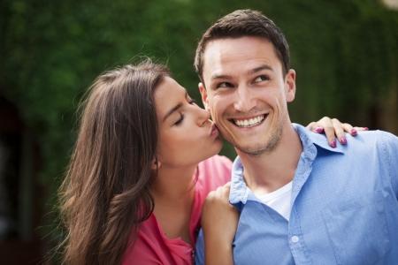 cheek: Young woman kissing her boyfriend on the cheek