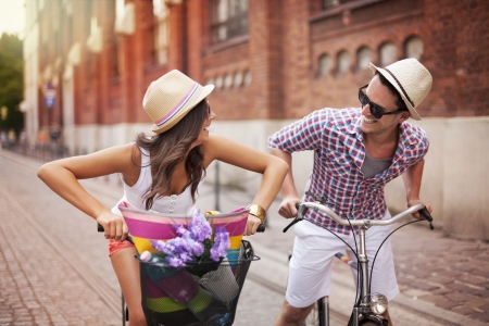 Happy couple chasing on bike in the street