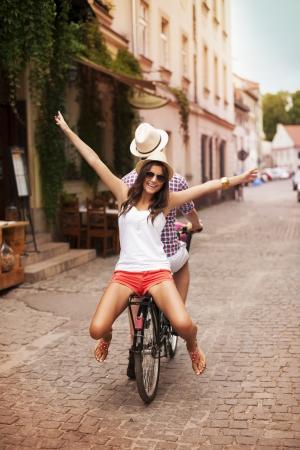 jovenes enamorados: Mujer joven feliz montando en bicicleta con su novio Foto de archivo