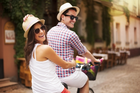 Happy couple riding a bicycle in the city street  Stock Photo
