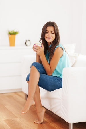 Pretty woman relaxing with cup of coffee at home Stock Photo - 21025477