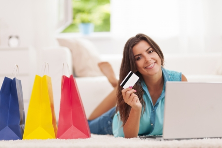 paying with credit card: Beautiful woman paying by credit card for shopping at home