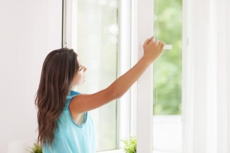 window open: Beautiful woman breathing freshness air