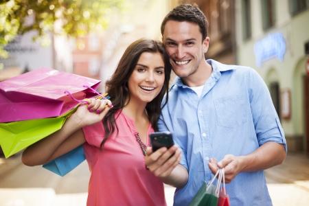 pareja abrazada: Pareja feliz con tel�fono inteligente durante las compras Foto de archivo