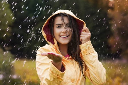 rain wet: Pretty young woman in yellow raincoat