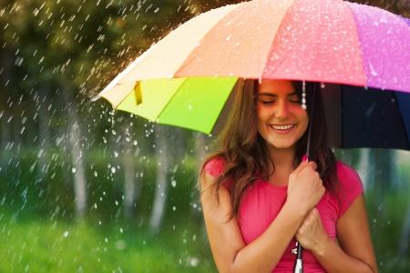 Mooie vrouw onder regenboog paraplu Stockfoto