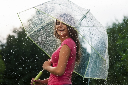 Young woman standing in summer rain with umbrella  photo