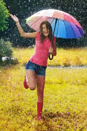 若くて美しい女性は雨の中で楽しい時を過す