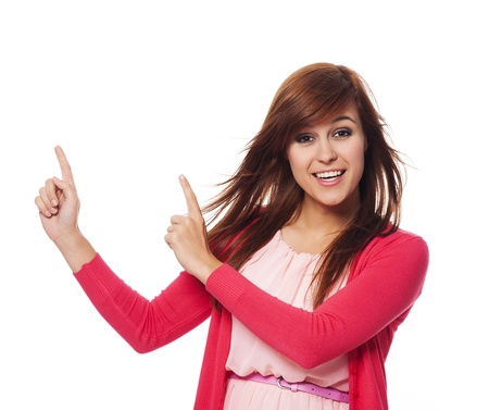 Beautiful woman in pink pointing at copy space  photo