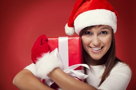 Woman holding christmas present next to her face photo