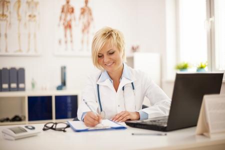 doctora: Joven y bella mujer m�dico que trabaja en su oficina