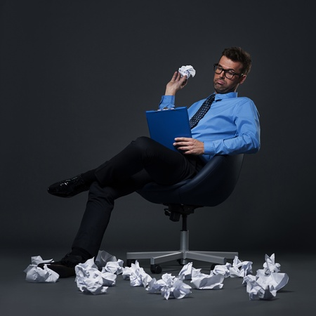 idea comfortable: Sitting businessman throwing a crumpled paper with bad ideas on the floor