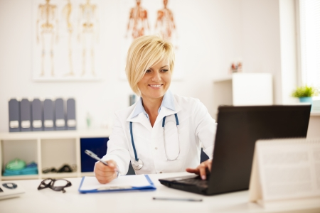 doctor writing: Checking medical results on laptop