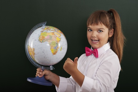 Schoolgirl with globe showing ok sign photo