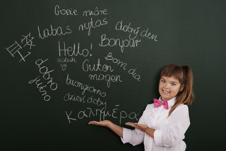 Schoolgirl presenting foreign phrases on blackboard photo