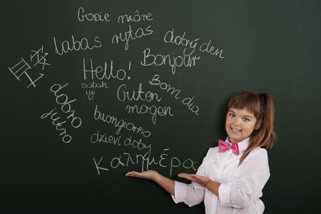 phrases: Schoolgirl presenting foreign phrases on blackboard Stock Photo