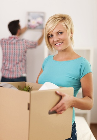 setup man: Woman carrying box with items for a new apartment