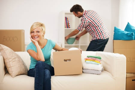 Beautiful woman resting on couch while her husband decorating their new living room Stock Photo - 22025496