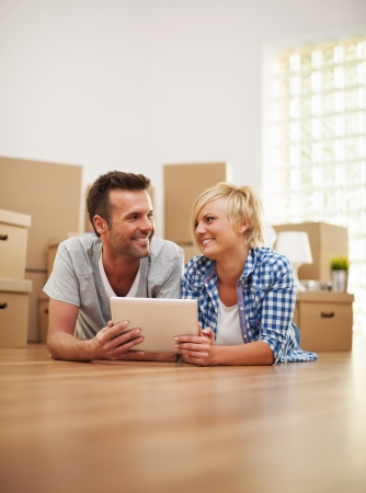Happy couple at the new apartment with digital tablet Stock Photo - 22678704