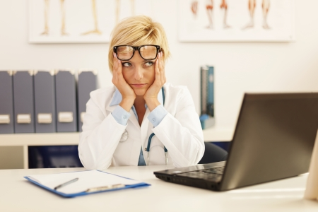 doctor stress: Desperate female doctor sitting at her office