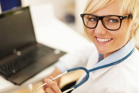 turning table: Portrait of beautiful blonde female doctor wearing glasses