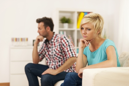 Unhappy young couple sitting in living room  photo