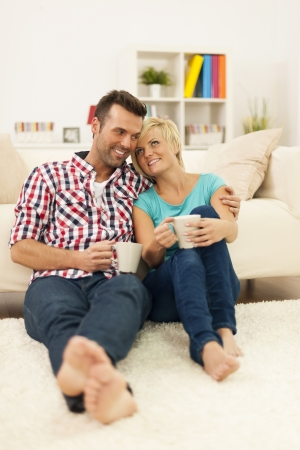 Happy couple sitting on the floor and drinking coffee photo