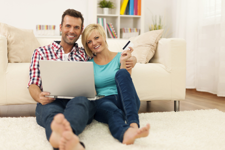 Happy loving couple sitting on the floor and using laptop and showing credit card photo