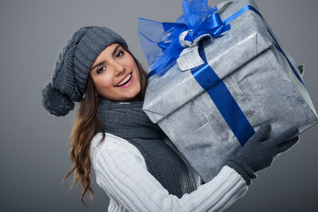 pompon: Happy woman wearing warm clothing holding big present